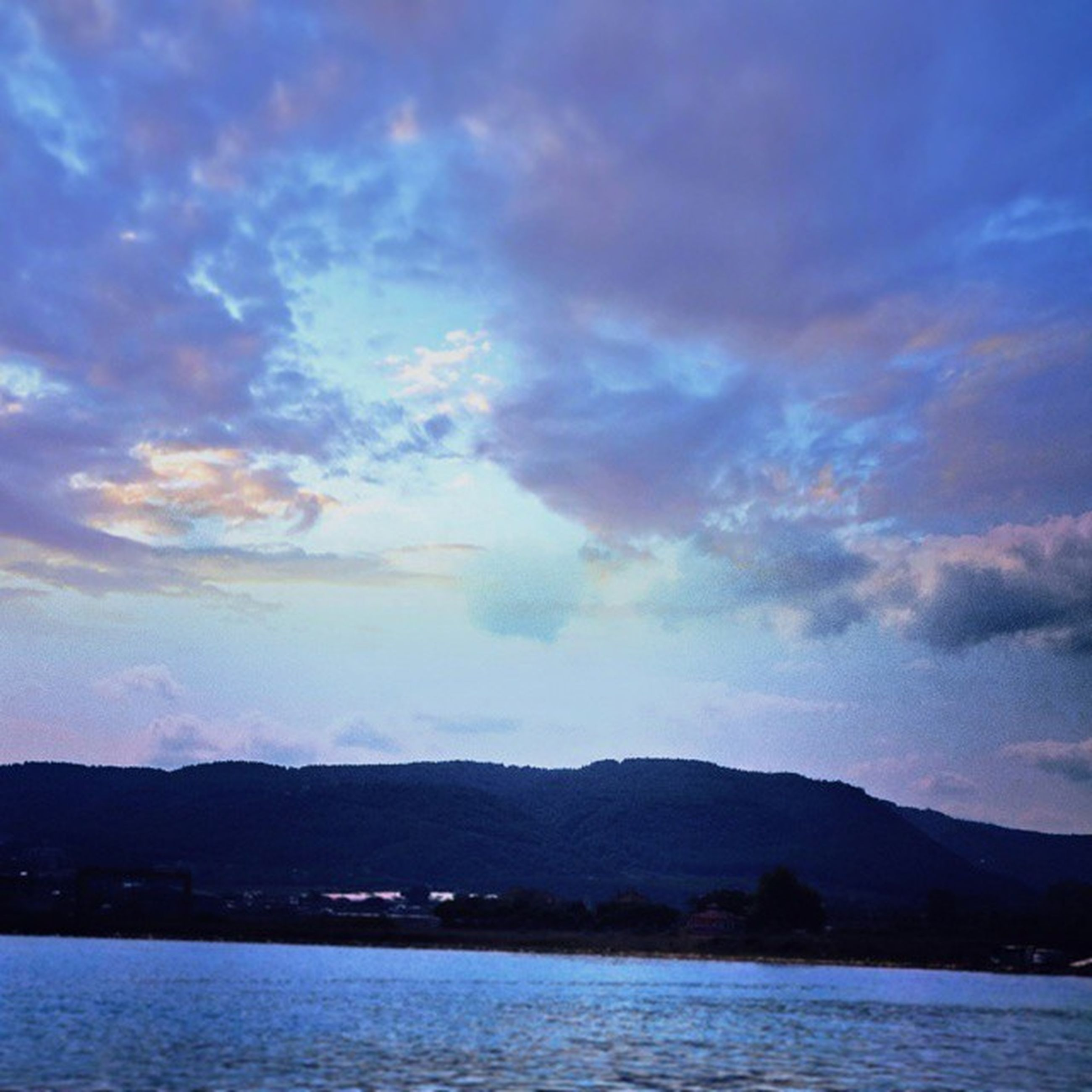 water, mountain, sky, tranquil scene, waterfront, scenics, mountain range, tranquility, beauty in nature, cloud - sky, lake, sea, nature, cloud, cloudy, idyllic, silhouette, dusk, river, non-urban scene
