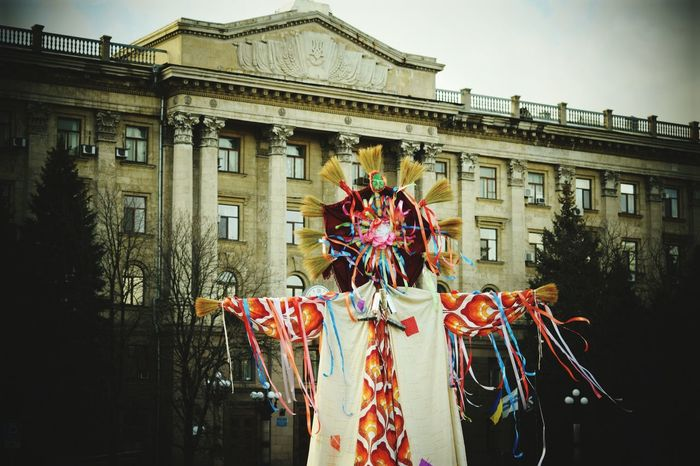 Building Exterior Architecture Built Structure Outdoors Arts Culture And Entertainment Travel Destinations City Day No People Festival Season Spring Has Arrived Carnival Crowds And Details Festival Slavic Maslenitsa Sun Sky Flag Tree Costume Cloud - Sky Blue Nature