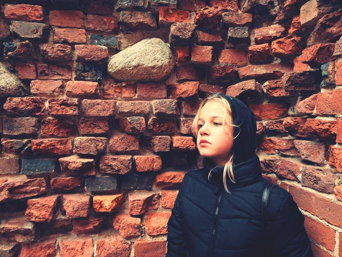 Girl looking away against brick wall