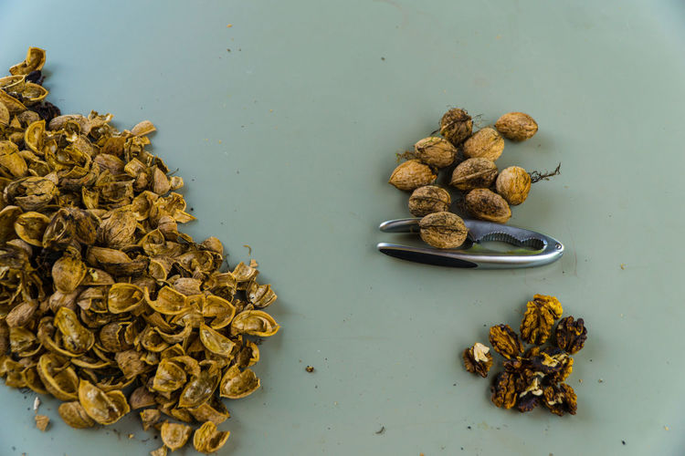 High angle view of walnuts with nutcracker on table