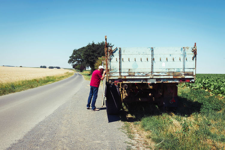 Man standing by truck at roadside against clear blue sky
