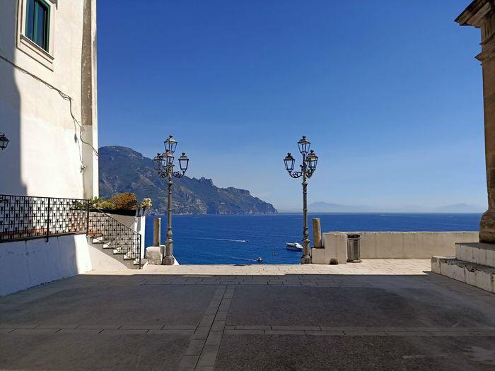 Street by sea against clear blue sky