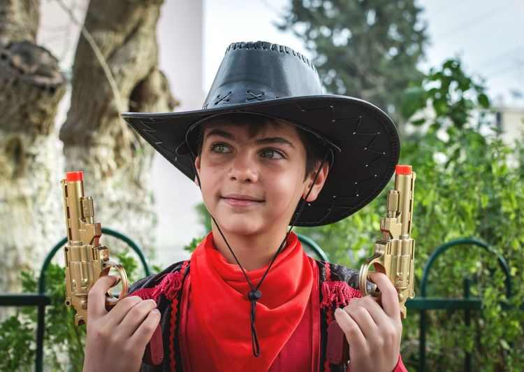 Close-Up Of Boy In Cowboy Costume Holding Toy Guns At Yard