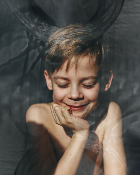 Close-up of shirtless boy smiling seen through glass