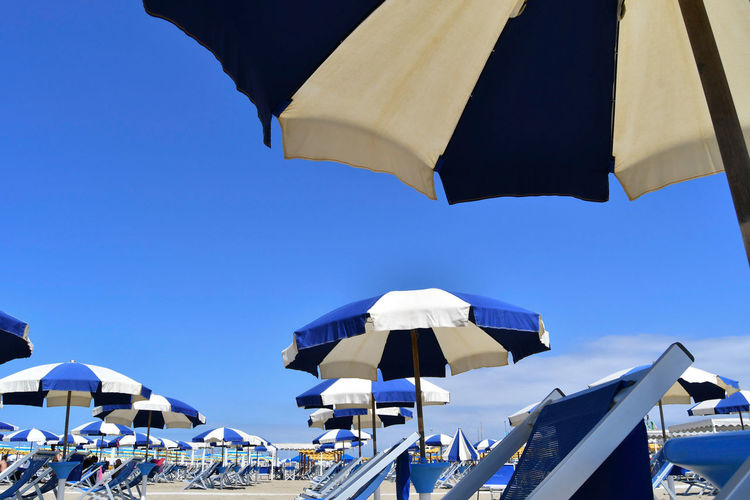 Low angle view of beach umbrellas against clear blue sky