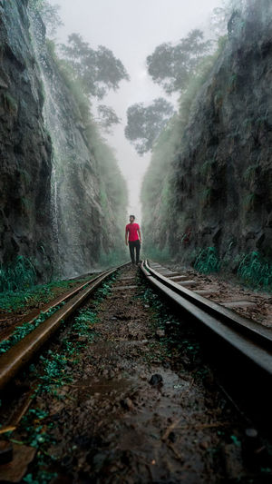Front view of person on railroad track between valley