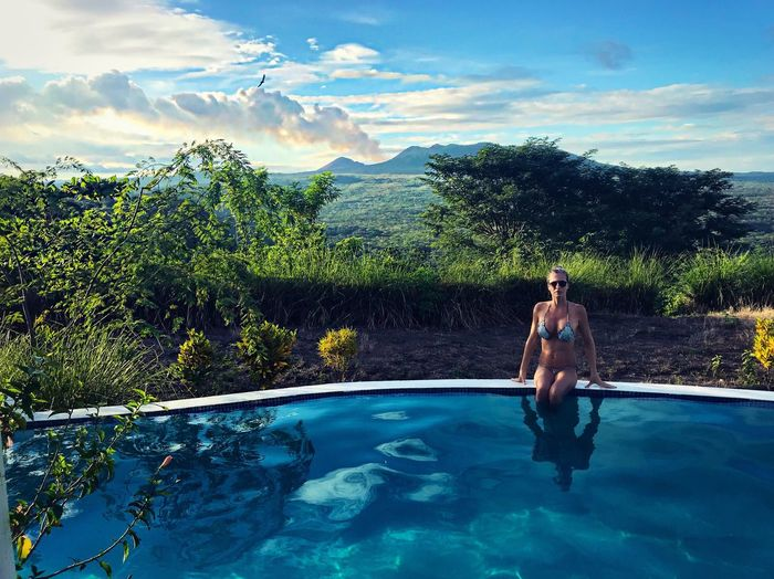 Young woman relaxing on infinity pool against sky