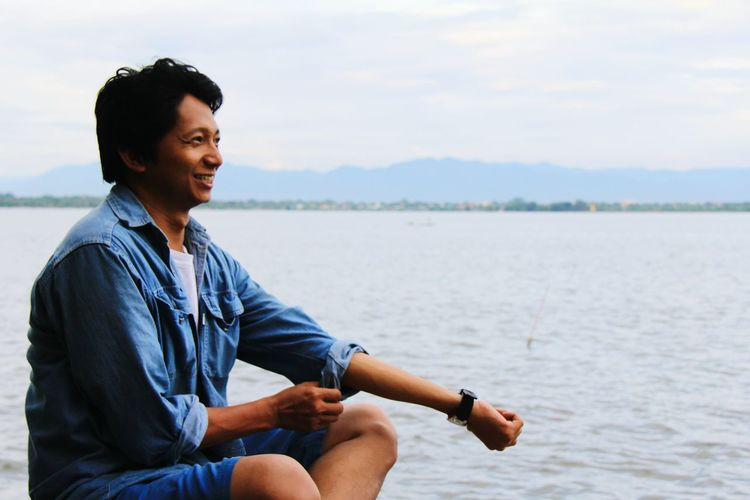 Smiling man sitting by sea against sky
