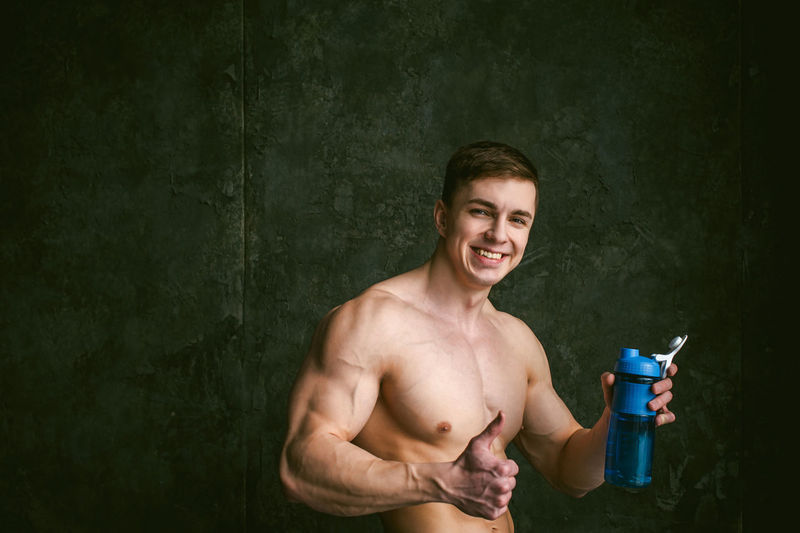 Portrait of shirtless man with bottle gesturing thumbs up against wall