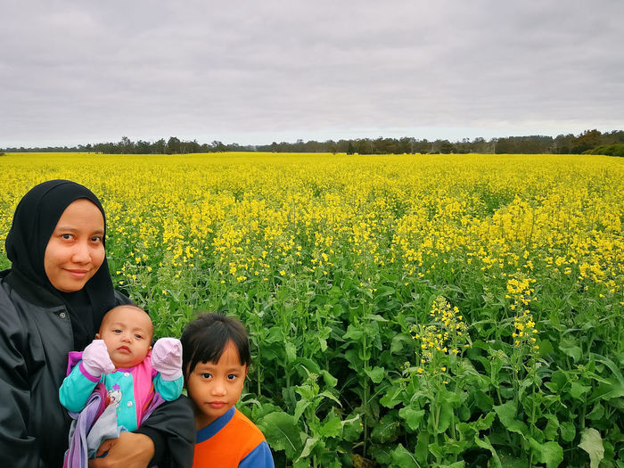 Portrait of woman with children against flowering plants