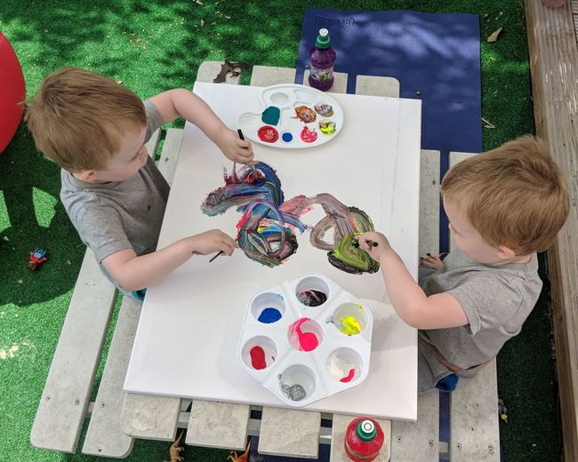 High angle view of siblings drawing on picnic table