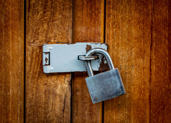Locked padlock with chain at wooden door background Wood - Material Safety Lock Entrance Protection Security Door No People Padlock Indoors  Closed Old Close-up Wood Brown Metal Hanging Wood Grain Latch