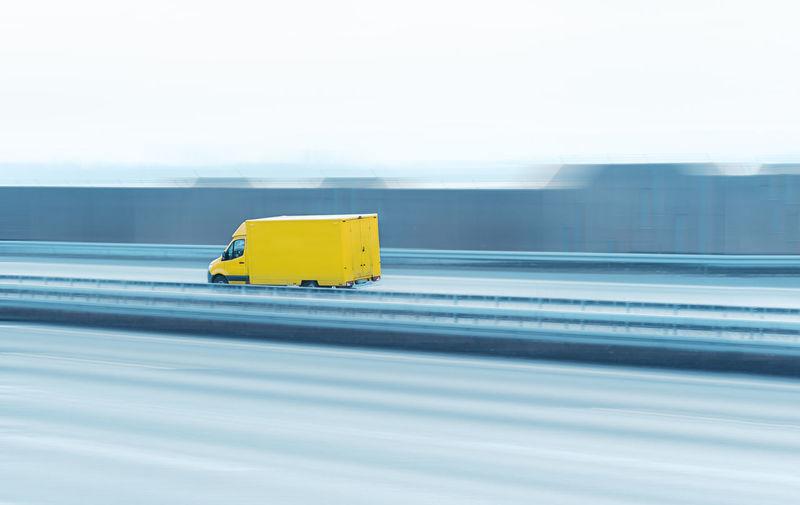 Yellow truck on bridge against clear sky