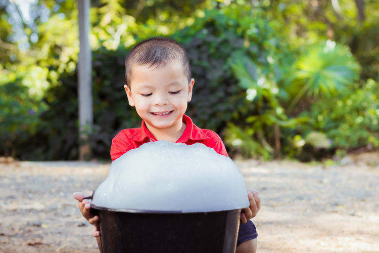Smiling boy with soap sud in bucket sitting on land