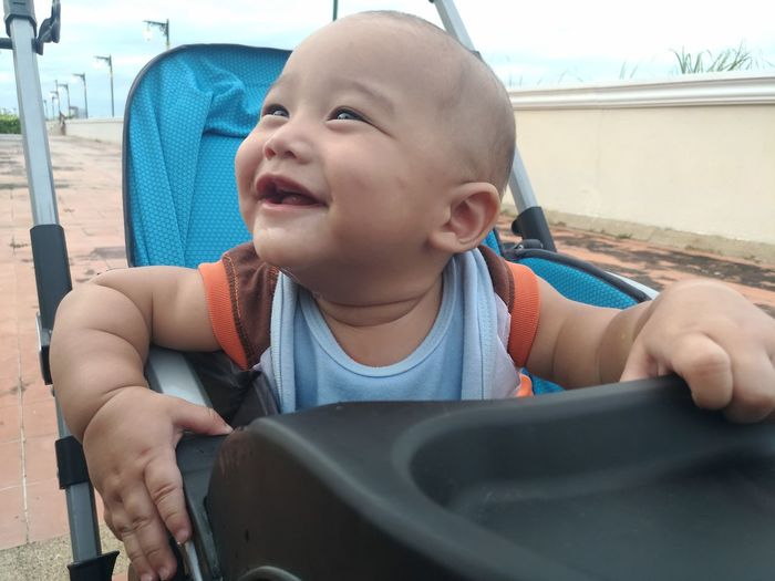 Smiling baby boy sitting in stroller