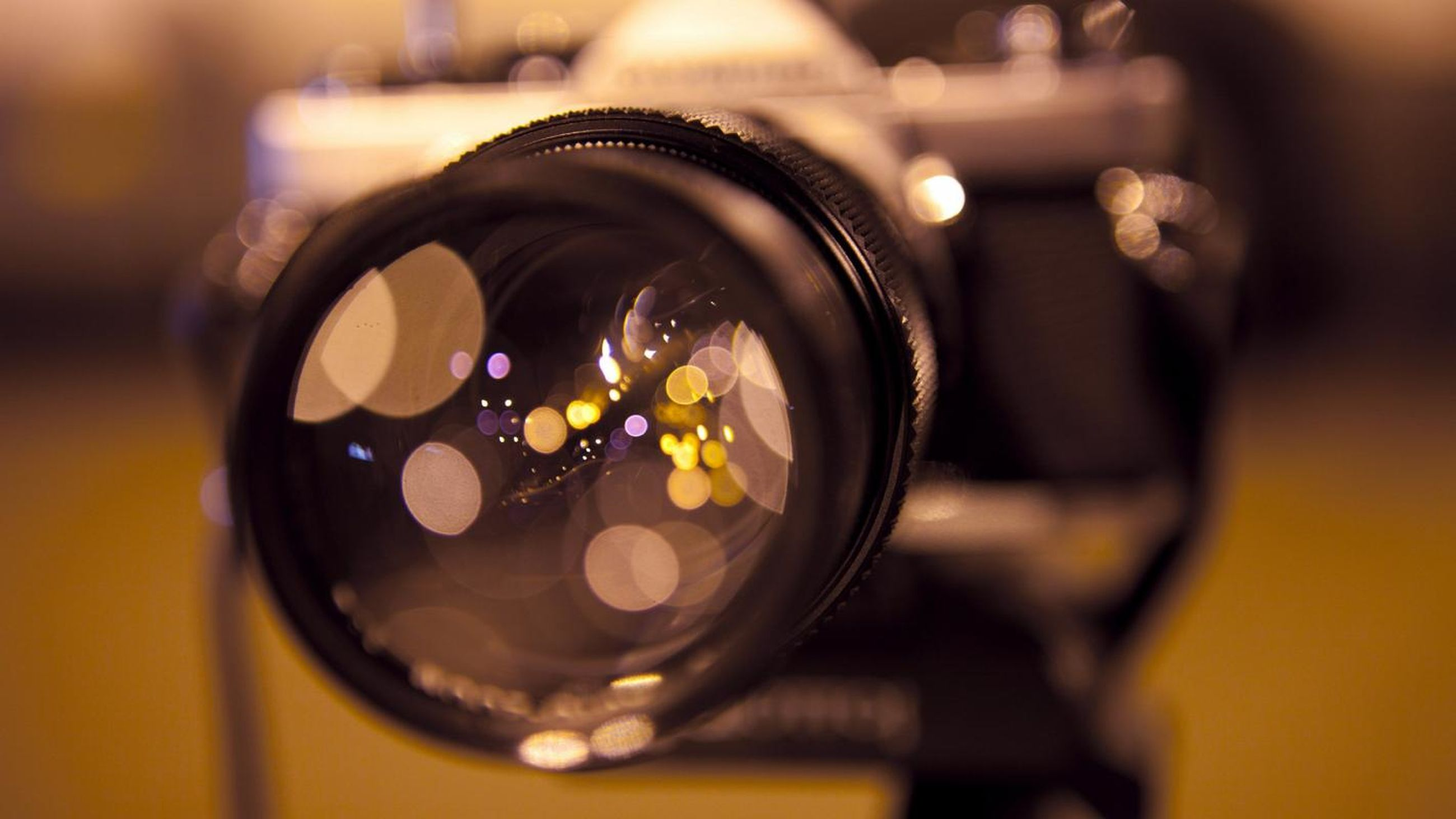 indoors, focus on foreground, close-up, selective focus, reflection, photography themes, glass - material, table, still life, circle, part of, technology, camera - photographic equipment, single object, shiny, land vehicle, cropped, holding