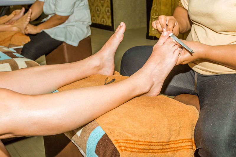 Section Of Women Doing Pedicure Of Customers