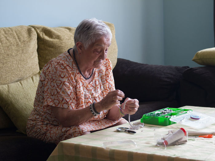 Senior woman making pearl necklace at home