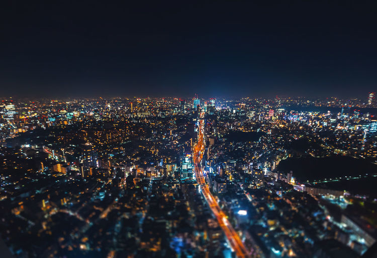 Aerial view of illuminated cityscape against clear sky