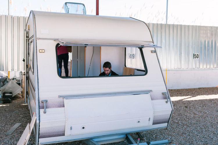 Man seen through window of camper trailer