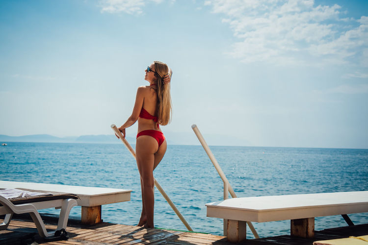 Young woman wearing red bikini while standing by sea against sky