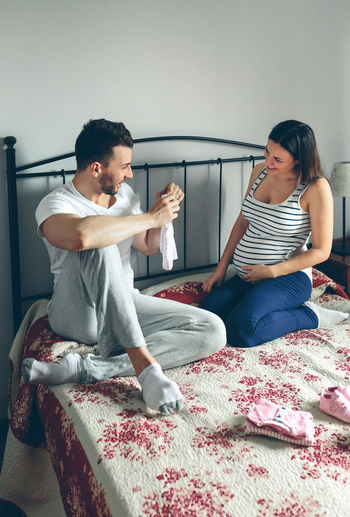 Young man showing baby clothes to her pregnant wife Baby Care Caress Family Love Man Maternity Mother Motherhood Wait Woman Caucasian Clothes Father Female Girl Holding Male Maternal Mom Pregnancy Pregnant Tummy Two People Vertical