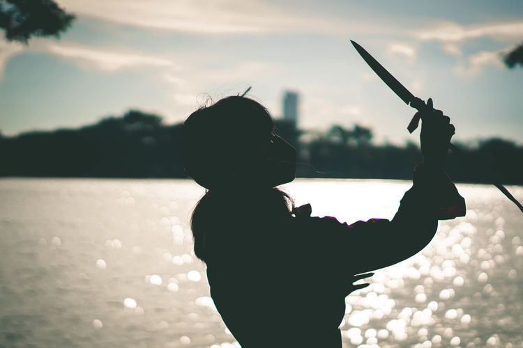 Woman practicing with knife against sea during sunset