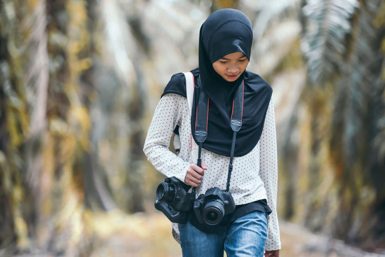 Teenage girl carrying camera against trees