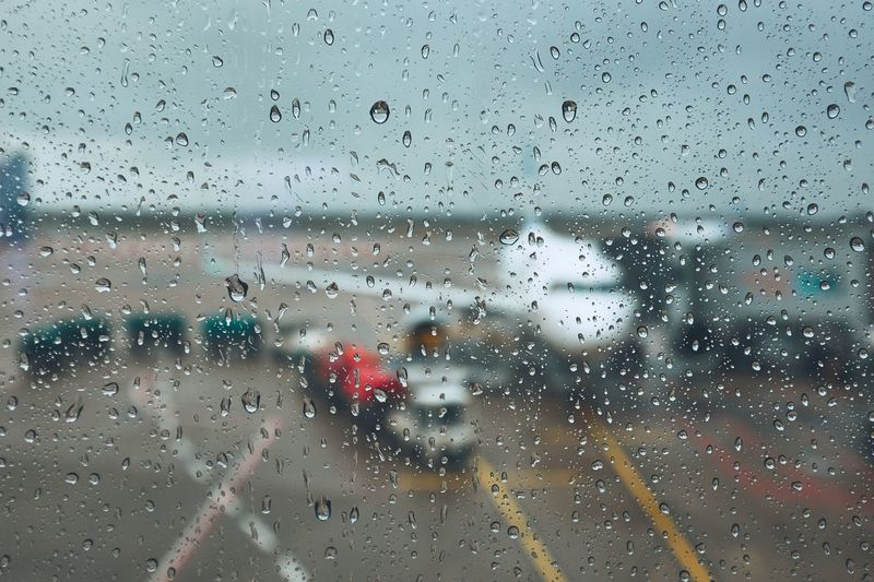 Storm at the airport. View of the airplane through rain drops. Themes weather and delay or canceled flight. Delayed Nature Plane Rain Storm Transportation Travel Weather Aircraft Airplane Airport Aviation Canceled Close-up Drop Flight Glass - Material Gloomy Problem RainDrop Safety Thunderstorm Water Wet Window