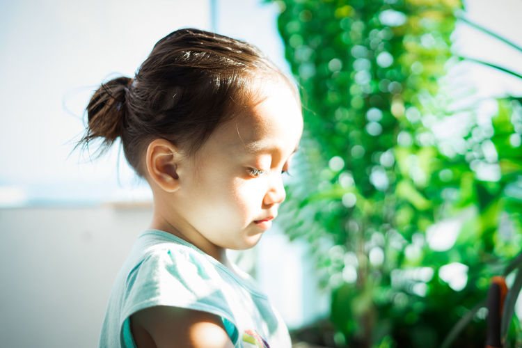 Close-up of girl standing by plants
