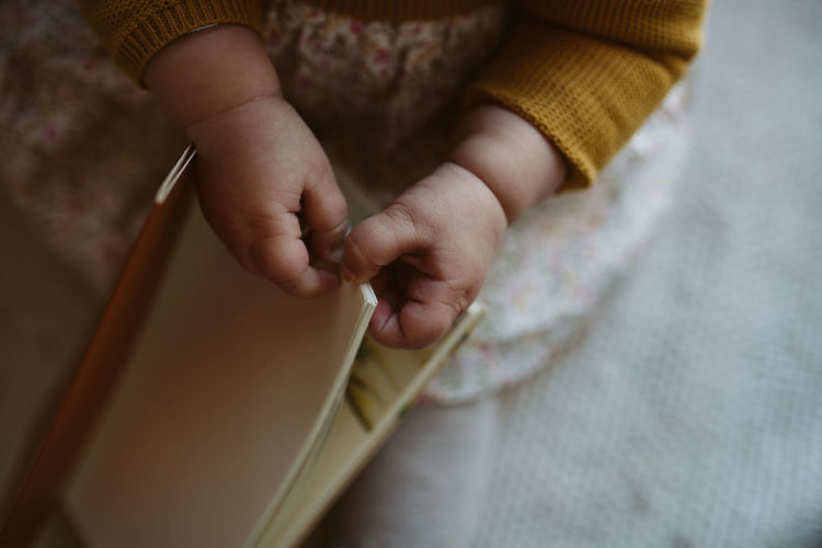 Midsection of baby holding book while sitting on bed