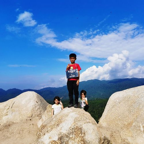 Portrait of boy standing with girls on mountain against sky