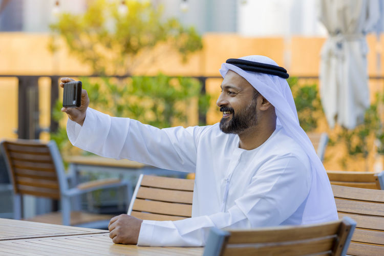 Man wearing traditional clothing taking selfie at outdoor cafe