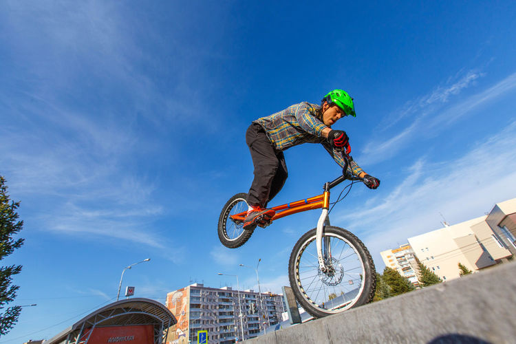 Low angle view of man performing bicycle stunt against sky