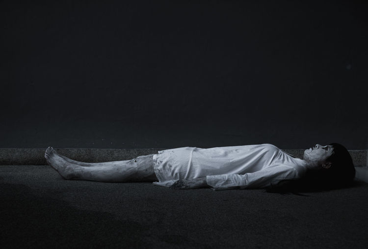 Side view of man sleeping against black background