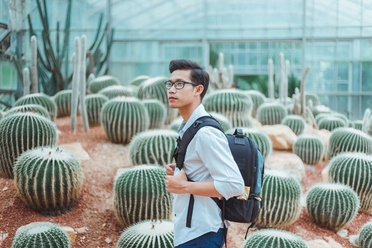 Full length of young man standing by plants