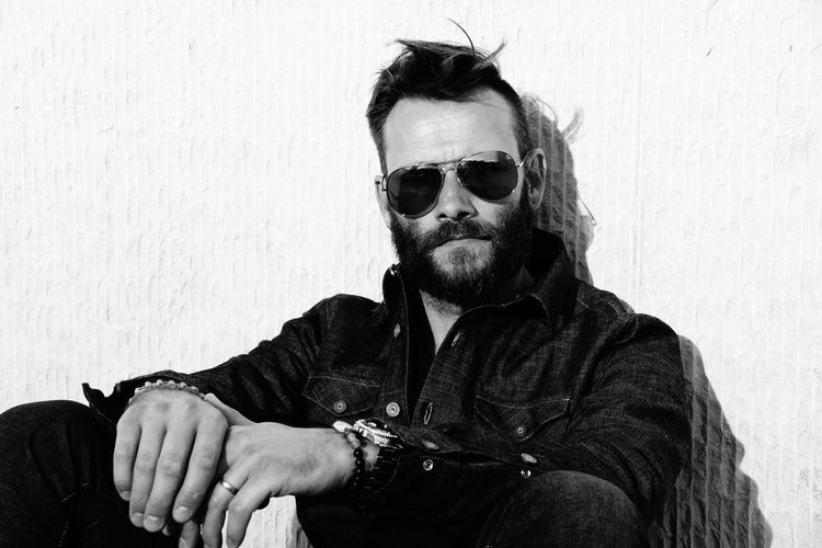 Portrait of man wearing sunglasses while sitting against wall