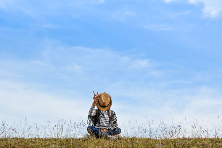 Girl sitting on grassy field against blue sky