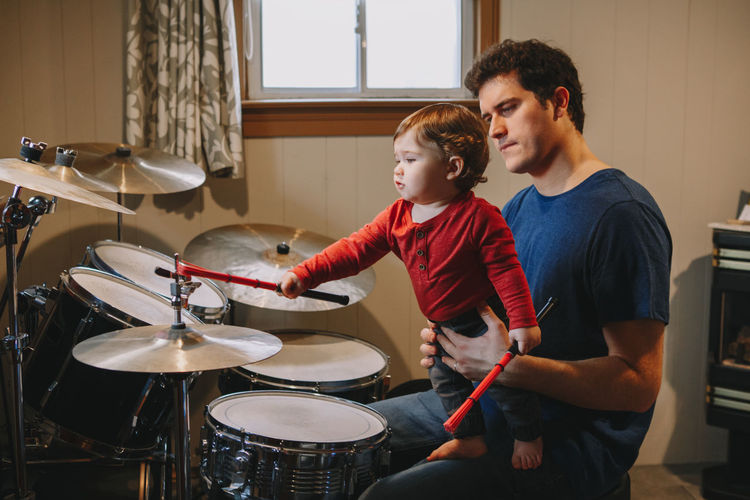Father holding cute baby son playing drums at home