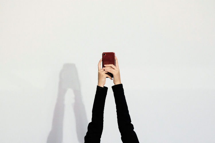 White Background One Person Copy Space Holding Technology Studio Shot Smart Phone Mobile Phone Wireless Technology Photography Themes Photographing Portable Information Device Women Communication Standing Indoors  Leisure Activity Activity Lifestyles Obscured Face Arms Raised The Minimalist - 2019 EyeEm Awards