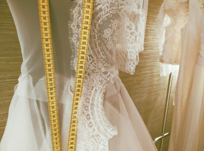 Close-up of wedding dress with tape measure