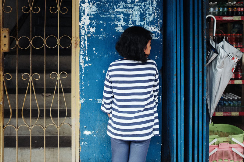A girl with white and blue line shirt over the blua wall in streets Adult Adults Only Blackandwhite Blend Day Indoors  One Person Only Women Pastel People Rear View Women Young Adult