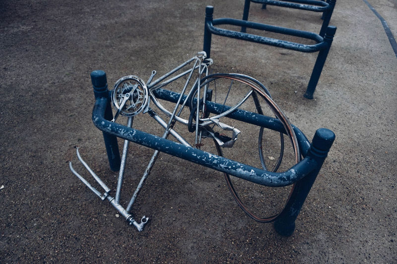 High Angle View Of Damaged Bicycle By Rack