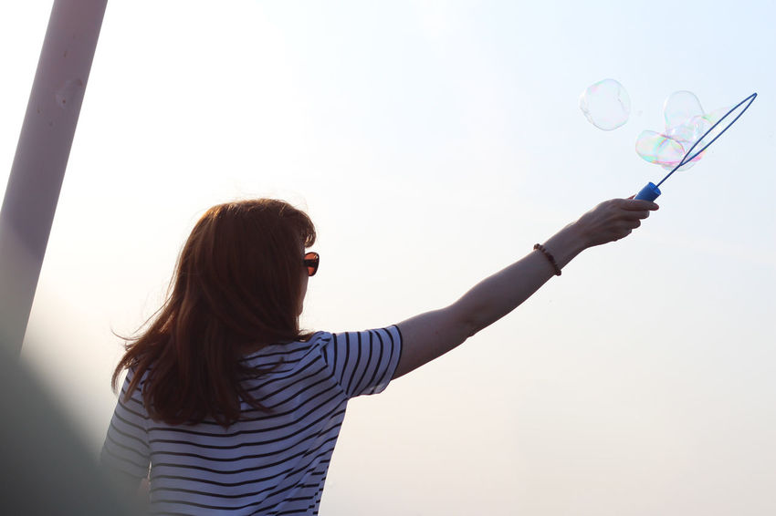 Young woman making bubbles Beauty In Nature Bubbles Casual Clothing Day Ginger Girl Gingerhair Leisure Activity Lifestyles Long Hair Non-urban Scene Person Scenics Silhouette Sky Sky And Clouds Standing Sunglasses Sunset Tranquility Waist Up Young Adult