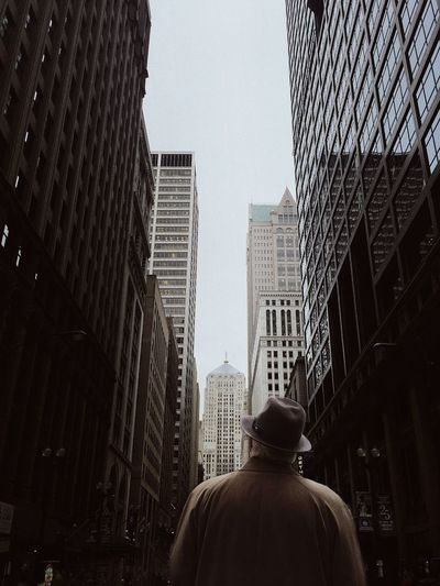 Low angle view of man in city against sky