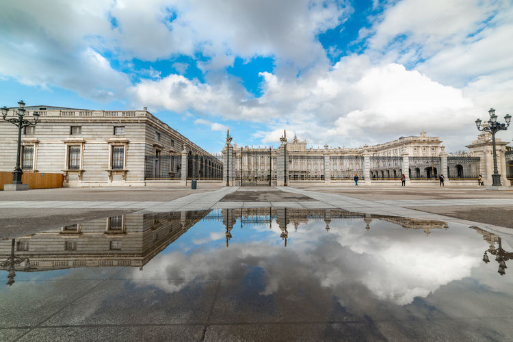 Reflection of historical building in puddle against sky