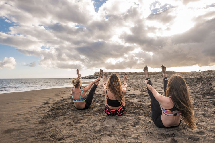 Rear View Of Young Women Practicing Yoga At Beach Against Cloudy Sky