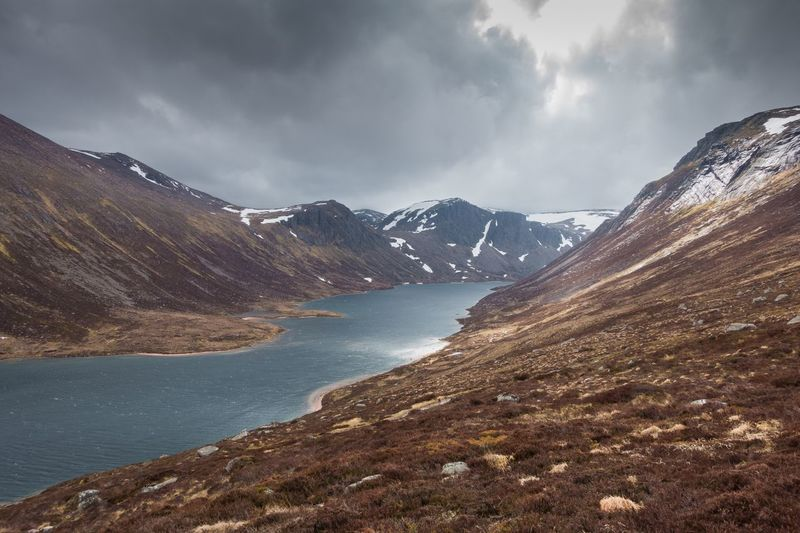 Idyllic shot of loch avon and mountains against cloudy sky