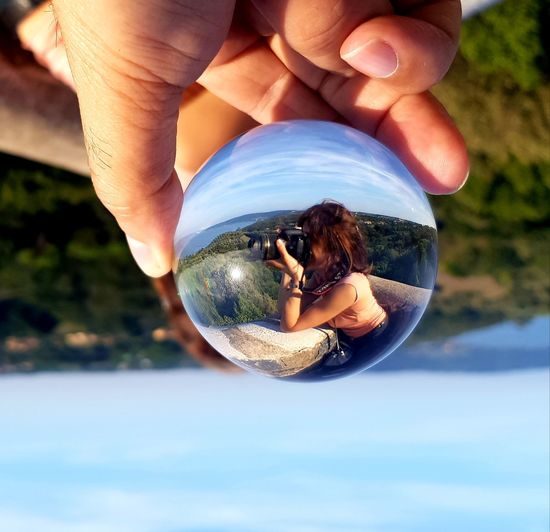 Midsection of person holding crystal ball with reflection