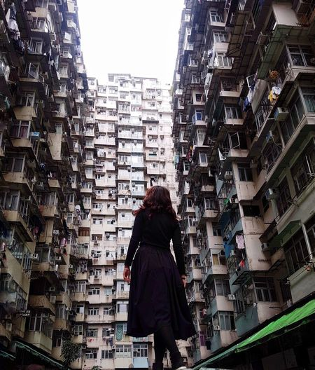 Rear view of woman standing amidst buildings
